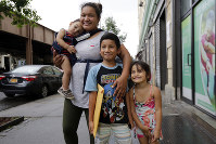 In this Friday, Aug. 3, 2018, photo, Nahun Eduardo Puerto Pineda, then 8, holding an envelope, from Honduras, poses for a photo with his mother, Eilyn Carbajal, and two siblings after being reunited with them at the Cayuga Center, in New York. (AP Photo/Richard Drew)