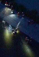 小学生が流された大和川の現場付近を捜索する消防隊員ら=大阪市住吉区で2018年9月23日午後6時13分、本社ヘリから山田尚弘撮影