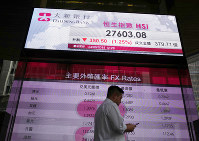 A man walks past an electronic board showing the Hong Kong share index outside a local bank in Hong Kong, on Sept. 24, 2018. (AP Photo/Vincent Yu)
