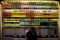 In this Nov. 27, 2012 file photo, a customer checks bottles of imported wine at a supermarket in Beijing. (AP Photo/Alexander F. Yuan)