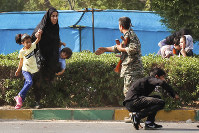 In this photo provided by Fars News Agency, a woman takes her children to shelter as an army member tries to help them, during a shooting at a military parade marking the 38th anniversary of Iraq's 1980 invasion of Iran, in the southwestern city of Ahvaz, Iran, on Sept. 22, 2018. (Fatemeh Rahimavian/Fars News Agency via AP)