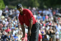 Tiger Woods motions for his putt for birdie to slow down as it passes the ninth hole during the final round of the Tour Championship golf tournament on Sept. 23, 2018, in Atlanta. (AP Photo/John Amis)