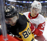 Detroit Red Wings' Evgeny Svechnikov, right, checks Pittsburgh Penguins' Sam Militec into the glass during the second period of an NHL preseason hockey game,on Sept. 23, 2018, in Pittsburgh. The Red Wings won 3-2. (AP Photo/Keith Srakocic)