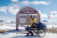 北極圏入りしたことを示す看板の前で=カナダ・ユーコン準州で、吉田正仁さん提供