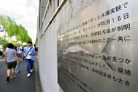 This photo taken on Sept. 6, 2018 shows a plaque hung on the exterior of the Tsukiji fish market that says fish exposed to radiation from a U.S. hydrogen bomb test in 1954 was brought to the market and buried on the grounds. (Mainichi/Naoki Watanabe)