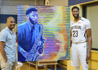 New Orleans Pelicans forward Anthony Davis (23) enjoys his portrait by artist Reuben Cheatem, left, during media day at the NBA basketball team's practice facility in Metairie, Louisiana, on Sept. 24, 2018. (AP Photo/Matthew Hinton)