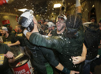 Oakland Athletics' Matt Joyce, center, is doused in the clubhouse celebration after clinching a wild card spot after the baseball game against the Seattle Mariners, on Sept. 24, 2018, in Seattle. (AP Photo/John Froschauer)