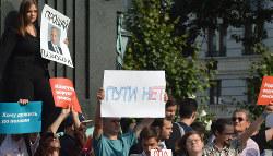 プラカードなどを掲げる抗議集会参加者たち