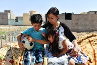 Laila Twalo Khidher, center, sits with her son Salar, left, and daughter Sara, in a town in the Duhok governorate of Iraqi Kurdistan, on Aug. 23, 2018. (Mainichi/Kenji Konoha)
