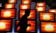 An attendee walks by a display of Hitachi flat panel televisions at the Las Vegas Convention Center during the 2007 International Consumer Electronics Show on Jan. 8, 2007 in Las Vegas. (Getty/Kyodo)