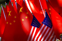 In this Sept. 16, 2018 file photo, American flags are displayed together with Chinese flags on top of a trishaw in Beijing. (AP Photo/Andy Wong)