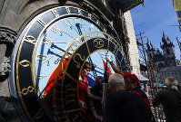 In this picture taken on Sept. 11, 2018, workers adjust the newly restored parts of the famed Prague's medieval astronomical clock in Prague, Czech Republic. (AP Photo/Petr David Josek)