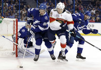 Tampa Bay Lightning defenseman Mikhail Sergachev (98) controls the puck in front of Florida Panthers right wing Evgenii Dadonov (63) during the first period of an NHL preseason hockey game on Sept. 25, 2018, in Tampa, Fla. Defending for the Lightning is Alex Killorn (17). (AP Photo/Chris O'Meara)