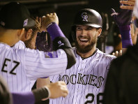 Colorado Rockies' David Dahl (26) is congratulated by teammates in the dugout after hitting a three-run home run against the Philadelphia Phillies during the third inning of a baseball game on Sept. 25, 2018, in Denver. (AP Photo/Jack Dempsey)