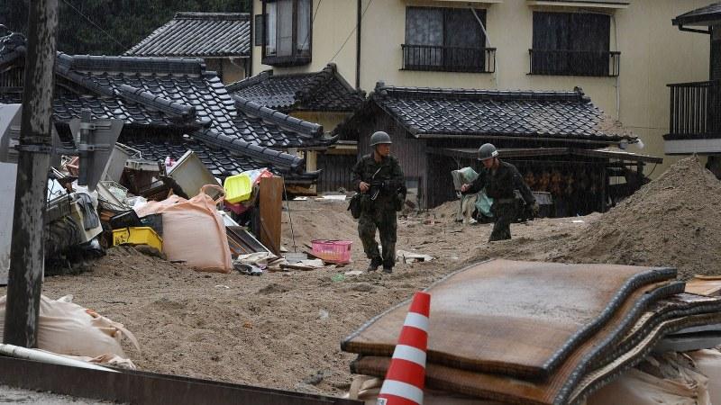 台風12号の影響で雨が降る中、土砂が残る住宅地を見回る自衛隊員= 呉市で2018年7月29日、西本勝撮影