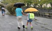 保護者に手を引かれて登校する児童たち=徳島市庄町5の加茂名小学校周辺で13日、岩本桜撮影