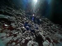 小型探査ロボットが23日に撮影した小惑星リュウグウの表面の画像。上部の白いものは太陽光=宇宙航空研究開発機構提供