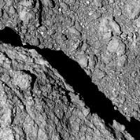 小惑星探査機「はやぶさ2」が小惑星リュウグウの高度64メートルから撮影した画像。左下は大きな岩の塊=宇宙航空研究開発機構提供