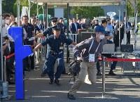 顔認証システム(左)の実証実験で、偽造IDで通過できず、逃走する不審者役の男性(右)=東京都江東区で2018年9月28日午後3時6分、手塚耕一郎撮影