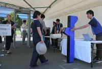 顔認証システムを使ったスクリーニング実証実験で、機器の前に進む関係者役の女性=東京都江東区で2018年9月28日午後2時7分、手塚耕一郎撮影