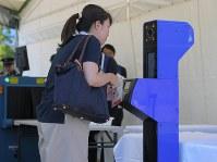 顔認証システムを使ったスクリーニング実証実験で、ADカードをかざす関係者役の女性=東京都江東区で2018年9月28日午後2時8分、手塚耕一郎撮影