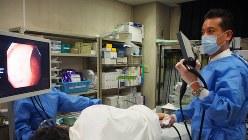 横になる患者に細い管を挿入して大腸にがんがないか調べる内視鏡検査=関東中央病院提供