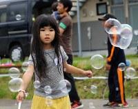屋外で遊び、作ったシャボン玉を見つめる少女=北海道安平町で2018年9月24日午後1時半、貝塚太一撮影