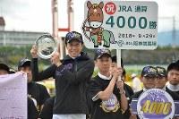 JRA通算4000勝を達成し、記念プレートを手に笑顔を見せる武豊騎手(中央左)。中央右は弟の武幸四郎調教師=兵庫県宝塚市の阪神競馬場で2018年9月29日午後3時19分、加古信志撮影
