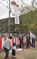 防犯カメラ設置でくす玉を割って祝う住民ら=滋賀県高島市マキノ町小荒路で、塚原和俊撮影