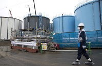 In this Feb. 23, 2017 file photo, an employee walks past storage tanks for contaminated water at Tokyo Electric Power Co. (TEPCO)'s tsunami-crippled Fukushima No. 1 nuclear power plant in Okuma, Fukushima Prefecture. (Tomohiro Ohsumi/Pool Photo via AP)