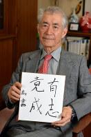 Tasuku Honjo holds a card reading