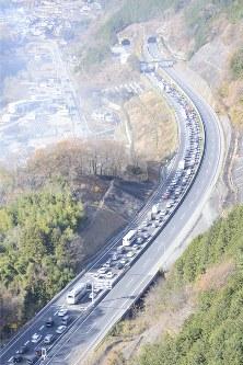 崩落事故があった中央道上り線の笹子トンネル入り口付近には、バス停と思われる場所に集まる人たち(下)。画面上はけが人を運ぶと思われるシート=山梨県甲州市で2012年12月2日午前10時56分、本社ヘリから
