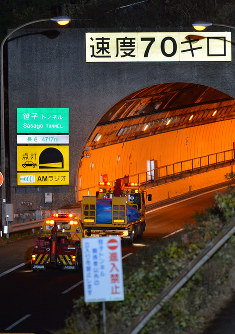トンネル天井崩落に巻き込まれた乗用車をシートにくるみ、笹子トンネルを出て下りのトンネルに向かう車両=山梨県大月市で2012年12月3日午後7時55分、西本勝撮影