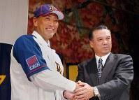 オリックスのユニホームを着て中村監督(右)と握手する清原=大阪市北区で2005年12月26日、貝塚太一写す