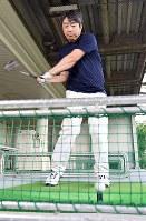 ゴルフの練習をする久保利明王将。まなざしは将棋と同様、真剣そのもの=大阪府吹田市で、山崎一輝撮影