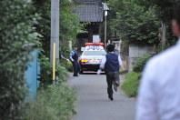 男が立てこもる住宅前に駆けつける捜査員。パトカーも止まっていた=埼玉県熊谷市石原で2015年9月16日午後5時39分、安藤いく子撮影