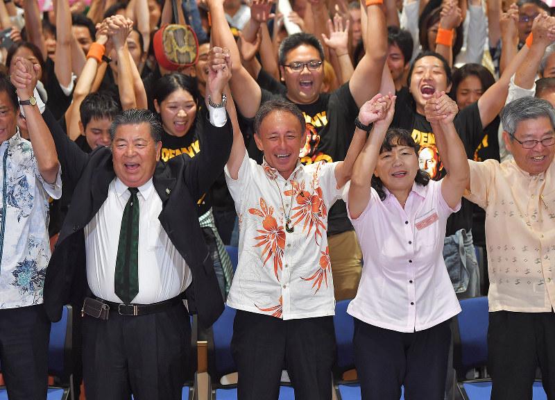 沖縄県知事選で当選を確実にし、万歳する玉城デニー氏(中央)=9月30日