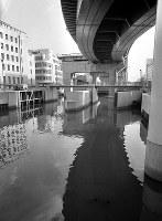 汚れた水たまりになって、やがて埋め立てられる運命にある西横堀川。上を阪神高速道1号線が走る=1965年10月1日撮影