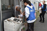 Students from Iwate Prefectural University, Chubu University, Ohio University and the Honjo International Scholarship Foundation hand out boxes of bottled water to a resident of the temporary housing unit located on the grounds of Yonesaki Junior High School in Rikuzentakata, Iwate Prefecture, on Sept. 29, 2018. (Mainichi/Alina Kordesch)