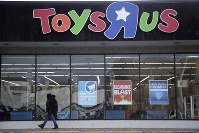 In this Jan. 24, 2018, file photo, a person walks near the entrance to a Toys R Us store, in Wayne, N.J. (AP Photo/Julio Cortez)