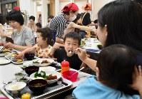 「みなと子ども食堂」で母親(手前)と一緒に食べる男の子。この日のメニューは、約20人のボランティアが作ったハンバーグ定食で子ども100円、大人300円。育児中の親たちの憩いの場でもある=東京都港区で2018年9月5日、丸山博撮影