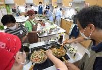 約50人分を料理するボランティアの人たち。毎回10~20人で、準備から片付けまで約6時間かかる。大学2年、中込由美夏さん(23)は「『ありがとう』と言ってもらえて達成感があります」=東京都港区の「みなと子ども食堂」で2018年7月4日、丸山博撮影