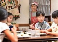 「だんだん ワンコインこども食堂」で楽しそうに食事をする子どもたちを見つめる近藤博子さん(奥)。子どもは100円でも10円でも、硬貨1枚で利用できる=東京都大田区で2018年9月20日、丸山博撮影