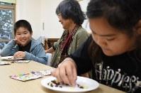 さまざまな形のチョコレートを組み合わせて遊ぶ小学生と祖母。製造企業の「クラシエ」が「こども食堂支援機構」を通じて全国各地に無償提供した商品だ=東京都港区の「みなと子ども食堂」で2018年7月4日、丸山博撮影