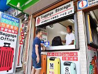 手荷物預かり所の岡西義友さん(右)と話す外国人旅行客=大阪市西成区で2018年9月28日、猪飼健史撮影