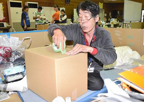 避難所から退所するため荷造りをする男性=岡山県倉敷市真備町上二万で、益川量平撮影