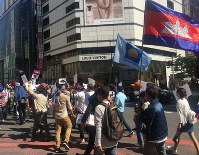 The Cambodian flag flies beside the flag for the main opposition party, the Cambodian National Rescue Party, which was dissolved by the country's Supreme Court in November 2017, during a protest march by Cambodian nationals in Japan on Oct. 7, 2018, in Tokyo's Shinjuku Ward. (Mainichi/Alina Kordesch)
