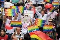 虹色のプラカードを掲げながら行進する「東京ラブパレード」の参加者ら=東京都新宿区で2018年10月8日午後3時38分、渡部直樹撮影