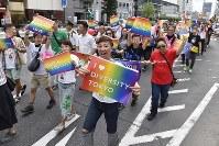 虹色のプラカードを掲げながら行進する「東京ラブパレード」の参加者ら=東京都新宿区で2018年10月8日午後3時50分、渡部直樹撮影
