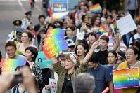 虹色のプラカードを掲げながら行進する「東京ラブパレード」の参加者ら=東京都新宿区で2018年10月8日午後4時38分、渡部直樹撮影